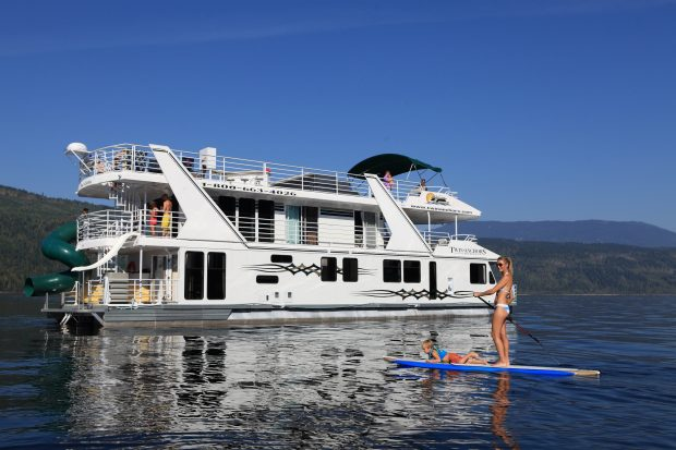 Paddleboating by a Twin Anchors Houseboat on the lake in Sicamous.