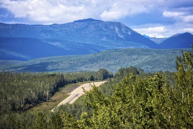 An aerial shot of the highway through the forests of Northern BC.